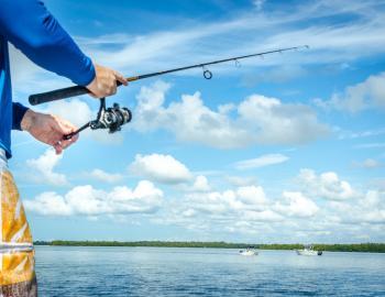 man in colorful board shorts flat fishing in florida
